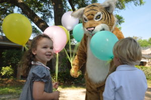 A young girl smiles at summer camp while she is handed a balloon.